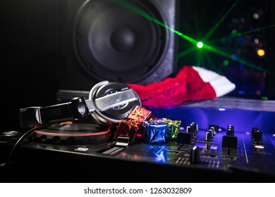 Dj mixer with headphones on dark nightclub background with Christmas tree New Year Eve. Close up view of New Year elements on a Dj table. Holiday party concept. Empty space