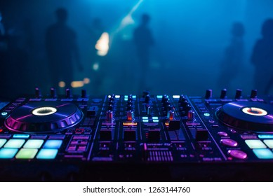 DJ mixer on the table background the night club and dancing people