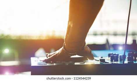 Dj mixing music outdoor at beach boat party festival  - Summer nightlife view of disco club at sunset - Focus on hand - Fun, millennials generation, youth lifestyle,entertainment and fest concept