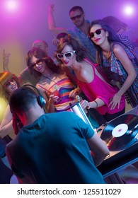 dj mixing music with turntables and headphones in front of young dancing people with sunglasses and cocktails surounded by colorful lights