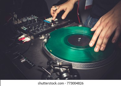 Dj mixing at night party inside night club - Disc jockey playing music with vintage vinyl records - Fun, retro, entertainment and fest concept
