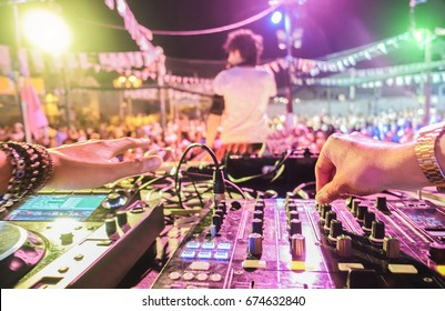 Dj mixing outdoor at beach party festival outdoor with crowd of people in background - Soft focus on center right hand - Fun, summer, youth, nightlife, music and entertainment concept - Retro filter