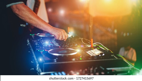 Dj mixing outdoor while streaming a online party festival during Coronavirus time - Alternative fest on isolation quarantine - Soft focus on hand - Fun, tech and entertainment concept