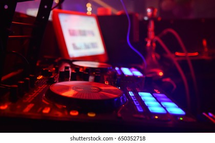 dj mixing table in night club red lights
