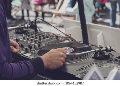 Dj mixing vynil records on open hair - view from the back - focus on the right hand, filtered image