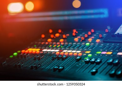 DJ Music mixing console with light bokeh.