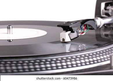 Dj needle on spinning turntable, closed-up on white