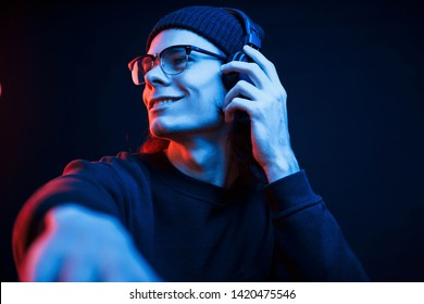 DJ on his job. Studio shot in dark studio with neon light. Portrait of serious man.