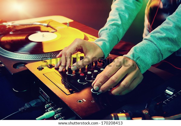 DJ operating a mixer and turntable.
