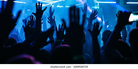 Dj party at nightclub. Crowd rave at the stage background