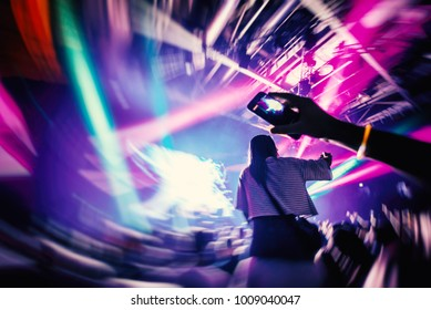 Dj party at nightclub. Girl sitting on shoulders of her boyfriend inside crowd. Special art effect
