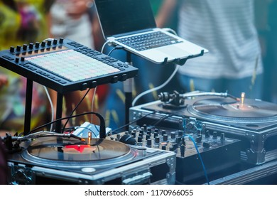 Dj place on party.Professional disc jockey setup on outdoor festival. Retro vinyl turntable player with analog disc,digital midi controller,sound mixer and laptop for playing musical tracks