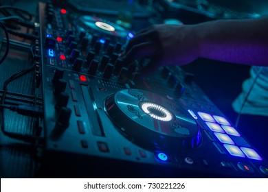 dj play with mixer in night club cyan tones