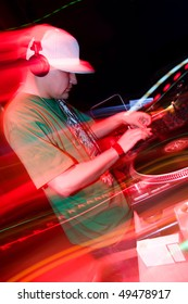 DJ playing music at a party in the nightclub. Disc jockey in headphones mixing tracks on vinyl records turntables. Blurred motion lights.