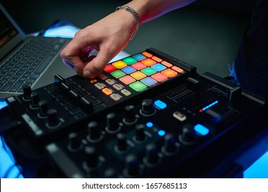 Dj plays beats on drum machine.Hip hop disc jockey playing on concert stage with professional midi controller device. Beat machine device for electronic music composer.