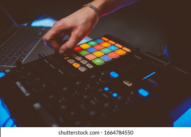Dj plays beats on drum machine.Hip hop disc jockey playing on concert stage with professional midi controller device. Beat machine device for electronic music composer.  vintage photo processing