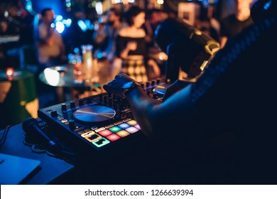 DJ plays live set and mixing music on turntable console at stage in the night club. Disc Jokey Hands on a sound mixer station at club party. DJ mixer controller panel for playing music and partying.