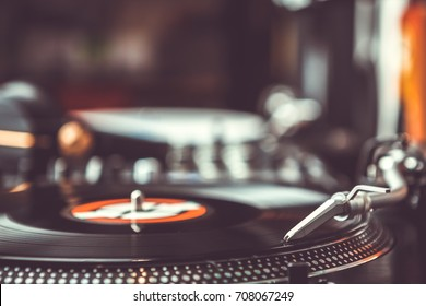 Dj plays vinyl records player with music disc.Turntables at hip hop party in night club.Professional hi-fi turn table equipment for disc jockey playing musical tracks on concert stage.Vintage djs gear