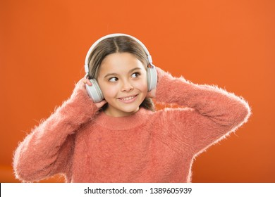 DJ, put the record on. Cute small child wearing DJ headphones. Little girl listening to music and dancing on silent disco in earphones. Adorable DJ girl. Enjoying music playing on DJ party.