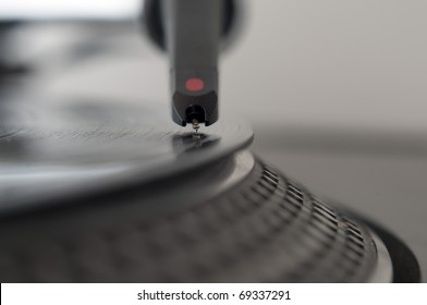 DJ record turntable. Macro closeup of the needle on a 12 inch vinyl LP playing hiphop techno rave beats.