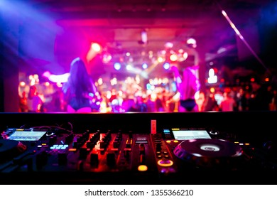 DJ remote on stage at the nightclub. background of dancing people.