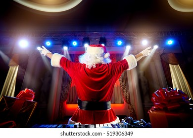 Dj Santa Claus for Christmas in the rays of light, with music at the event is back, put his hands up.