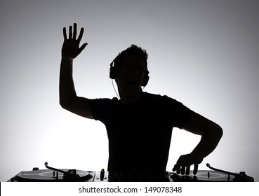 DJ silhouette. Silhouette of DJ gesturing and spinning on turntable