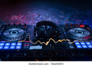 DJ sound equipment at nightclubs and music festivals, EDM, . Party concept, sound technique. DJ playing on the best, famous CD players. Dj mixer with headphones at nightclub bokeh background.
