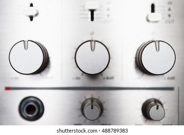 DJ sound mixer and amplifier regulators. Close up, macro. Professional audio equipment for mixing music at concert, party event.