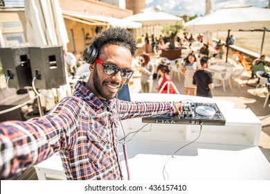 Dj taking a selfie while mixing music on a deejay set in a club, people dancing