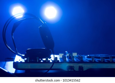 DJ turntables in a nightclub. Disco light in the club. Headphones on the remote.