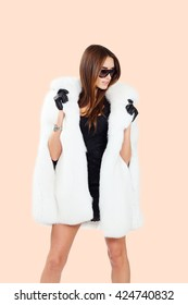 DJ woman with earphones in fur coat and sunglasses poses on isolated studio background. Fashion look