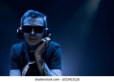 DJ work in a nightclub. Disco light in the club.