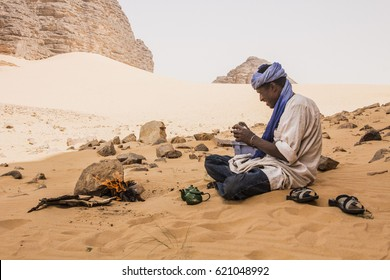 DJANET, ALGERIA - April 6, 2017: Tuareg man preparing traditional tea on the fire in Sahara desert, Djanet, Algeria