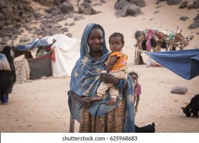 DJANET, ALGERIA - April 6, 2017: Tuareg woman with baby near her home in Sahara desert, Hoggar mountains, Djanet, Algeria
