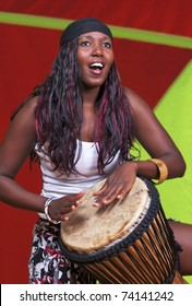 Djembe drummer set against a colorful background