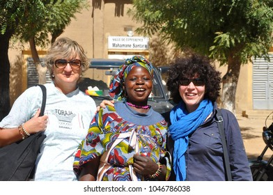 Djenne, Mali - December, 28, 2014: Tourists with local people at market of Djenne