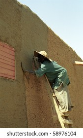DJENNE, MALI - JANUARY 14: Peul man repairs the mud wall of a house on January 14, 2006, Djenne, Mali. The mud brick walls must be repaired once a year.