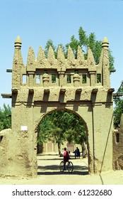 DJENNE, MALI - JANUARY 16: Local people cross the mud-built gate on January 16, 2006, Djenne, Mali. Sahelian mud-architecture is famous in Djenne, a UNESCO World Heritage site.