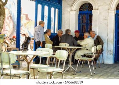 DJERBA, TUNISIA - APRIL 16: Group of men play cards in a coffee shop in Houmt El Souk in Djerba, Tunisia, on April 16, 2018