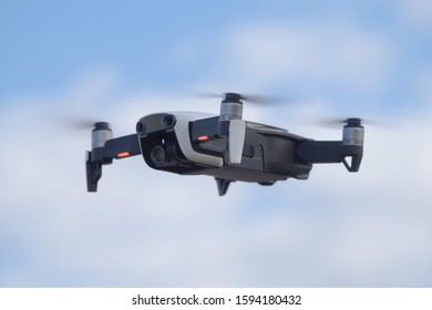 DJI Mavic Air small drone with four propellers flying in the air