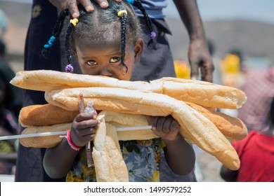 """Djibouti / Djibouti - June 03 2014: poor girls holding bread and chocolate aided by """" Ayadi relief """" from Bahrain"""