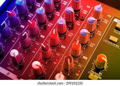 djs mixing console under colored dico lights