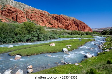 Djuku river and red rock formations in Tien Shan mountains, Kyrgyzstan