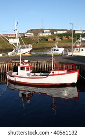Djupivogur - small fishing town in Iceland. Ships in harbor. Water reflection.