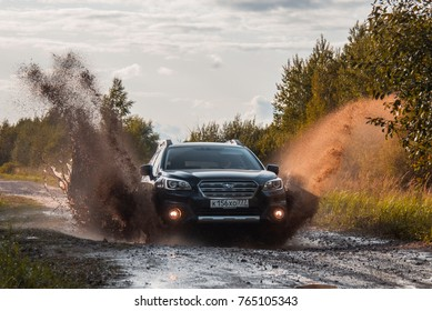 Dmitrov, Russia -September 9, 2017 Subaru Outback Suv rides through a puddle with spatter