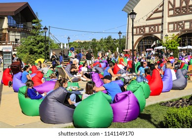 Dnepr city, Ukraine. May 28, 2018.  People rest on chairs bags of green, blue, purple, gray and red colors during the festival of food in Dnipro city.  Armchair bag.  Dnepropetrovsk, Dnipropetrovsk
