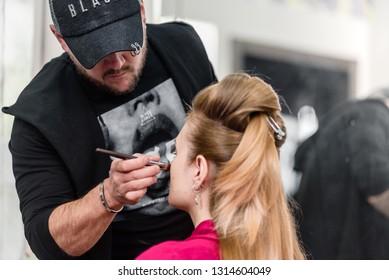 Dnepr, Ukraine- September 11, 2018: male visagist doing make-up. Open workshop master class of hairdressing Maya Norkina