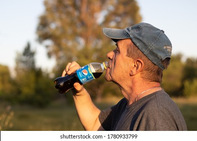 DNEPRO, UKRAINE - July 11, 2020. Signor Caucasian drinks Pepsi from a plastic bottle on a green lawn against the background of trees on a bright sunny day. Portrait with a blurred background.