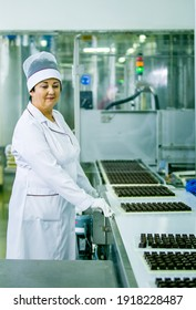 Dnepropetrovsk, Ukraine - 03.10.2016: Sweets factory. Sweets production process. A woman technologist monitors the work of an automatic line and checks the quality of products.